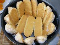 3 - Peler à vif les mandarines restantes. Tremper très rapidement les biscuits dans le fond de rhum ou de fleur d'oranger. Les disposer dans un moule à charlotte sur les bords et dans le fond. Verser une couche de crème, puis répartir des quartiers de mandarines et poser une nouvelle couche de biscuits. Renouveler l'opération jusqu'à terminer par une couche de biscuits. Réserver au réfrigérateur pendant 12h minimum.