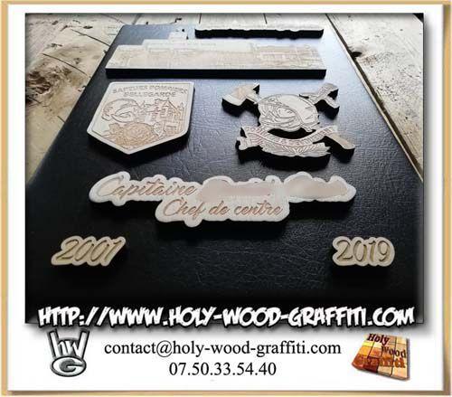 Les différentes pièces de bois gravées sont en relief sur le fond du tableau en simili cuir noir