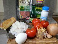 1 - Réunir vos ingrédients. Nettoyer, laver et éponger les calamars. Faire chauffer dans une casserole du lait et le verser bouillant sur la mie de pain émiettée. Bien écraser et malaxer à la fourchette. Peler, hacher l'oignon et l'ail, en réserver une moitié de chaque pour la suite de la recette. Découper le jambon cru en petits morceaux, en garder 2 tranches sans les découper pour la décoration.