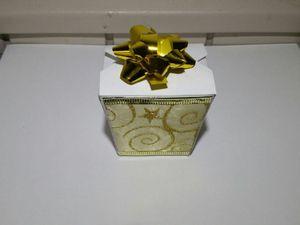 2 - Vos pliages effectués, remonter les côtés de la boîte et coller les languettes de côté à l'intérieur. Décorer maintenant une ou plusieurs faces de la boîte avec le ruban doré pour l'habiller. Vous pouvez aussi choisir d'autre décorations selon vos goûts. Coller enfin une rosace en bolduc sur le couvercle.