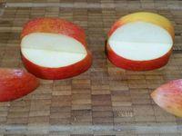 3 - Laver et essuyer les pommes. Découper la grosse pomme en gardant un peu plus de la moitié. Recouper en 2 quarts, ôter la partie trognon. Entailler les 2 quartiers comme sur la photo de façon à obtenir une bouche ouverte. Badigeonner la chair de la pomme au pinceau de jus de citron pour qu'elle ne noircisse pas. Insérer dans la bouche des pommes les amandes effilées pour matérialiser les dents des monstres. Dans l'autre pomme, détacher 4 billes de chair à l'aide d'une cuillère parisienne. Enfoncer une petite pique en bois dans chaque bille et les piquer sur le haut des bouches (Cf photo). Insérer des petits bonbons ronds de couleurs différentes dans les billes de pomme qui représenteront les yeux.