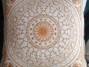 Un cuscino in lino,  con un motivo che sembra un rosone gotico, ricamato  in giallo con vari punti di ricamo tradizionale