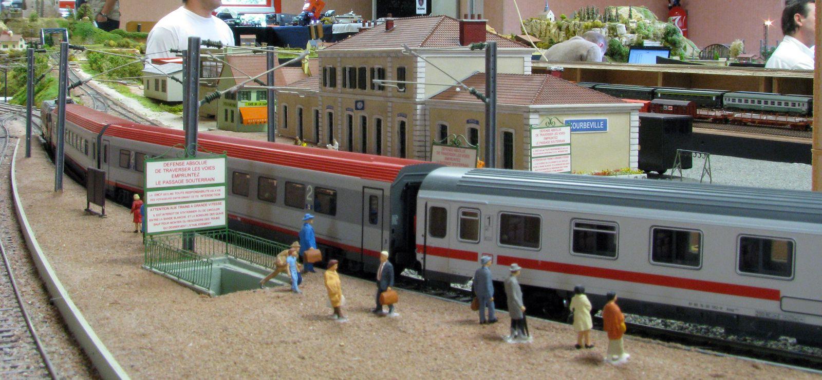Passage sans arrêt d'un train composé de voitures de la DB en gare de Courbeville.