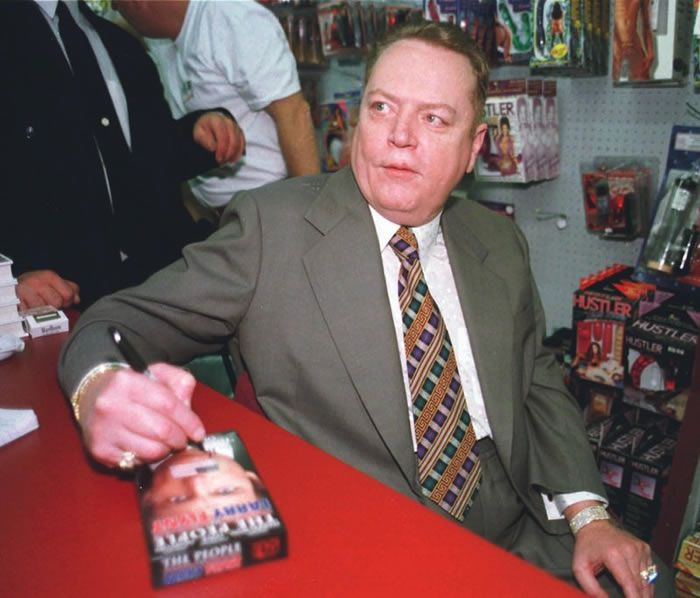 "FILE - ""Hustler"" Magazine publisher Larry Flynt signs a copy of ""The People Vs. Larry Flynt"" in his downtown Cincinnati ""Hustler"" store on April 30, 1998. Flynt, who turned ""Hustler"" magazine into an adult entertainment empire while championing First Amendment rights, has died at age 78. His nephew, Jimmy Flynt Jr., told The Associated Press that Flynt died Wednesday, Feb. 10, 2021, of heart failure at his Hollywood Hills home in Los Angeles. (AP Photo/Tom Uhlman, File)"