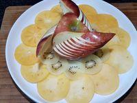 1 - Presser le 1/2/citron et réserver le jus. Découper la pomme rouge selon le modèle de notre vidéo (voir article précédent ou lien ci-dessus).  A l'aide d'un pinceau citronner la pomme découpée pour éviter qu'elle ne s'oxyde. Peler et découper en fines rondelles le kaki, puis les tailler à l'emporte-pièce rond (pour un rendu plus esthétique). Faire de même avec le kiwi. Prendre un plat de service, y déposer la pomme au centre. Installer tout autour les fines tranches de kaki et de kiwi. Peler à vif le pomelo rose.