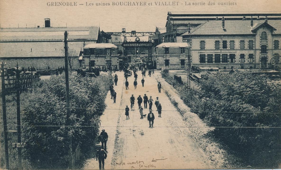 Etablissement  Bouchayer-Viallet (EBV) : sortie de l'usine donnant sur le cours Berriat. Le portique et les 2 petites maisons l'encadrant existent toujours ainsi que le batiment administratif à droite et le halle en arrière plan à droite