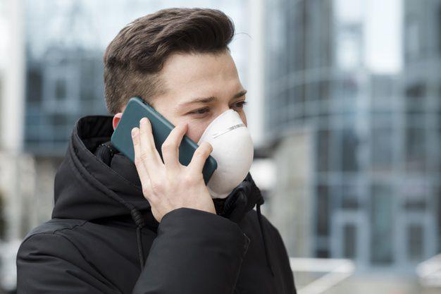 Homme qui téléphone avec un masque