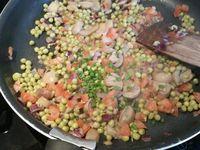 2 - Verser un filet d'huile d'olive dans une poêle, laisser chauffer et y faire revenir l'oignon rouge. Ajouter successivement les champignons, les dés de tomates et les petits pois, bien mélanger et laisser revenir quelques minutes. Incorporer un peu de ciboulette et persil ciselés et assaisonner avec sel et poivre. Réserver et laisser tièdir. Etaler la pâte feuilletée.