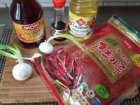 1 - Décortiquer les crevettes, les couper en 2 ou 3. Emincer l'oignon blanc (y compris la partie verte), réserver. Mettre dans un bol la sauce soja, le vinaigre de cidre, la poudre de piment coréenne, et le sucre. Mélanger bien l'ensemble.
