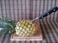 1 - Trancher un bel ananas en deux dans le sens de la longueur, puis chaque moitié à nouveau en deux en conservant bien les feuilles à leur extrémité