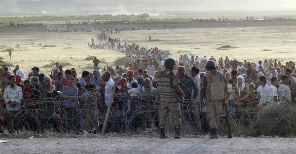 Turkish soldiers stand guard as Syrian refugees wait behind the border fences. 100,000 Syrian Refugees Fleeing Isis Attempt to Enter Turkey In 24 Hours. Sep 21, 2014.
