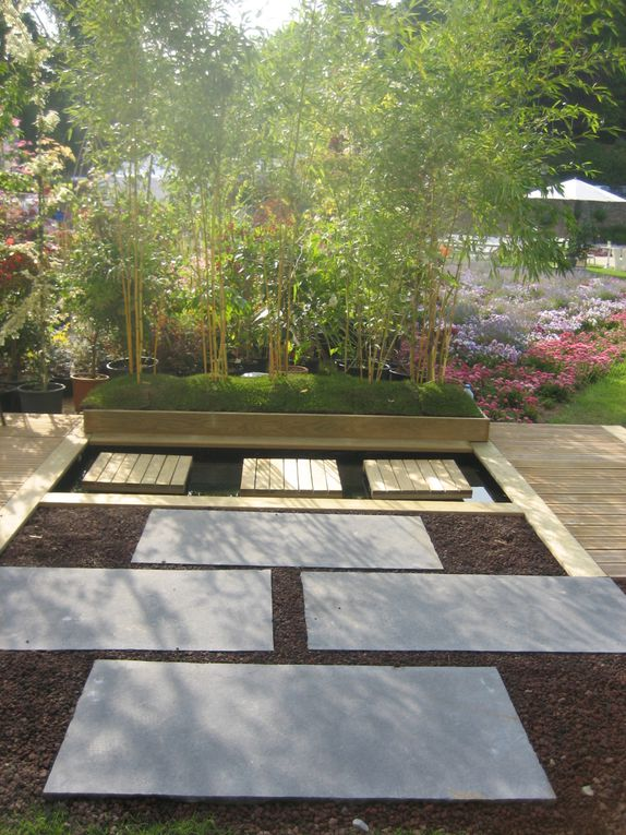 Arbor Minéral, paysagiste sur Vannes(56) a créé au salon Vannes Côté Jardin, un aménagement de jardin comprenant une terrasse en bois, un bassin avec son pas sur l'eau et une allée en pierres. Arbres nuages et mobilier contemporain (Fermob)