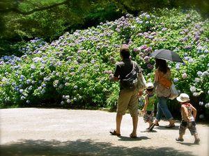Notez le style vestimentaire typique de l'été de la jeune mère de famille : longs gants, ombrelle foncée afin de se protéger du soleil