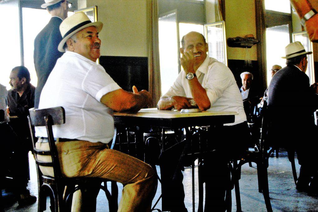 """Le café grec est une institution -typiquement masculine: lieu de jeu, de passage, de détente, de débat politique, on peut y rester des heures avec une consommation. On y boit ... du café, essentiellement et du grec, c'est-à-dire avec le moût en décoction, après qu'il a été chauffé lentement dans un briki, récipient en cuivre ou en fer blanc et qu'il a moussé. Avec du sucre, on le commande """"glyko"""", légèrement sucré """" metrio"""", et sans sucre """"sketo""""; à déguster lentement, servi avec un verre d'eau. Il résiste encore à la mode de l'expresso ou du nescafé, souvent servi aux touristes."""