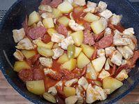 3 - Dans la même sauteuse, faire suer l'ail et l'oignon jusqu'à ce qu'il devienne translucide, ajouter les rondelles de chorizo, déglacer au vin blanc et laisser réduire de moitié, puis incorporer les tomates, les herbes de Provence, le bouillon, et le sucre, laisser mijoter quelques minutes. Pendant ce temps, tailler les olives vertes, peler et couper les pommes de terre en gros morceaux. Ajouter dans la sauteuse les morceaux de poulet, couvrir et laisser cuire à feu doux 10 à 15 mn,  ajouter les pommes de terre, les olives et laisser mijoter à couvert sur feu doux 35 mn. Ajouter un peu d'eau en cours de cuisson si nécessaire. Rectifier l'assaisonnement si besoin, et servir de suite.