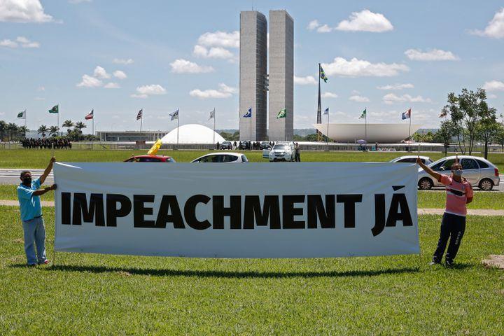 Des manifestants ont déployé une banderole pour protester contre la gestion de la pandémie par Jair Bolsonaro, le 23 janvier 2021, à Brasilia. (SERGIO LIMA / AFP)