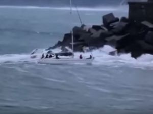 A sailboat, entering an harbour, capsized by a gigantic wave in rough seas