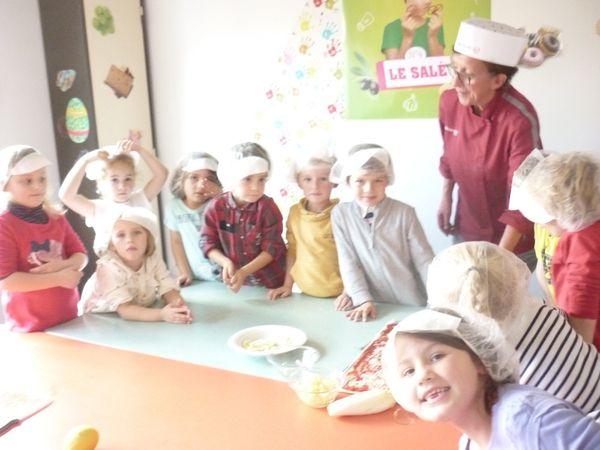 Avec Carole, notre cuisinière, les maternelles préparent une pizza ... Bon appétit !
