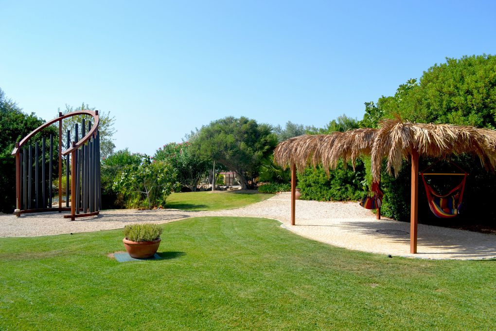 """THE GARDENS -  Are set on one hectar of land providing several diferent relaxation areas such as the unique """" ARCH of SOUND """" , pathways for walks with water streams, green areas and a lake."""