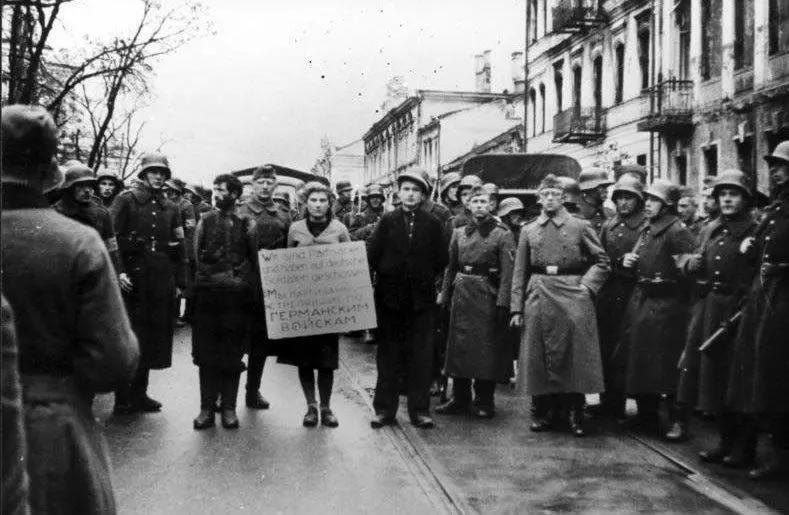 """Masha Bruskina, une infirmière faisant partie de la résistance soviétique, est conduite dans les rues de Minsk, en Biélorussie, avant sa pendaison, le 26 octobre 1941. Elle doit porter une pancarte avec l'inscription """"Nous sommes les partisans qui tirons sur les soldats allemands"""". © Wikimedia/Bundesarchiv"""