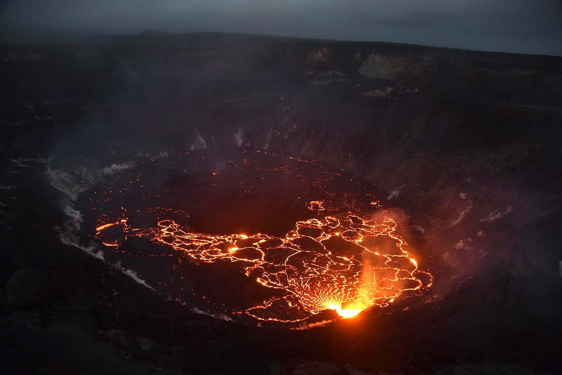 Lava fountain activity continues from the western vent of Halema'uma'u in the summit caldera of Kīlauea, seen at dusk on October 10, 2021, from the western edge of the crater. Only the western half of the lake surface is active; the eastern half is covered with a cooled and solidified crust. USGS image by B. Carr.