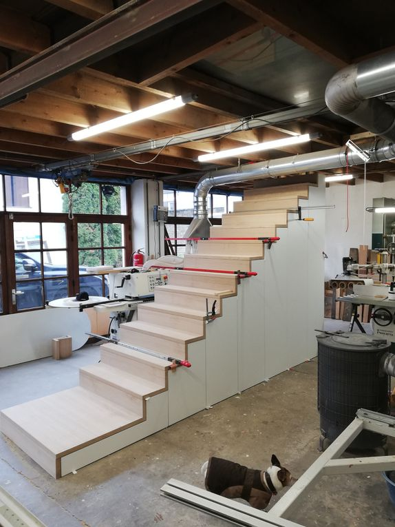 Escalier droit en chêne massif avec marche et contre marche ainsi que la 1ère marche type palière. Finition blanchit ultra léger et vernis PU 2 composants. Dessous d'escalier avec portes en stratifié coloris blanc pour un accès rangement.