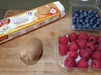 1 - Laver et sécher les fruits. Peler le kiwi, couper en deux dans le sens de la longueur et ensuite le tailler en fines tranches dans le sens de la largeur, décaler légèrement les tranches et les enrouler sur elles-mêmes. Poser le kiwi sur un biscuit palet breton. Disposer les myrtilles sur un autre palet breton. Superposer les deux compositions, décorer en déposant une framboise sur le haut du dessert, saupoudrer la framboise d'un peu de sucre glace.  Placer un découpe-ananas sur le côté d'un plat de service noir rectangulaire, saupoudrer de sucre glace pour créer une décoration en éventail. Décorer avec quelques myrtilles et framboises et déposer votre dessert sur l'autre côté du plat. Disperser sur le plat quelques brisures de palet breton en décoration.