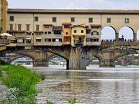 """Plus vieux pont de Florence, le Ponte Vecchio, monument emblématique de Florence et passage obligé de tous les amoureux, respire l'Histoire et transporte chaque touriste dans la dimension temporelle qui lui convient le mieux....se caller au milieu du pont, à mi chemin entre l'Arno et la ville, permet de s'échapper dans les traverses de l'Histoire au temps des intrigues de la cours des Médicis et de l'époque originelle du pont, jadis, une rue commerçante populaire avec les tanneurs et les bouchers. Mais ces métiers, trop olfactifs et incommodants pour les petites narines de la bourgeoisie locale, sont devenus sous la pression politique, un lieu plus """"noble"""" et raffiné avec les orfèvres et autres bijoutiers..."""