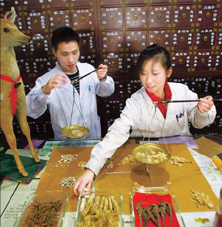 Two herbalists at Hedantang Pharmacy in Chaoyang district weigh TCM ingredients