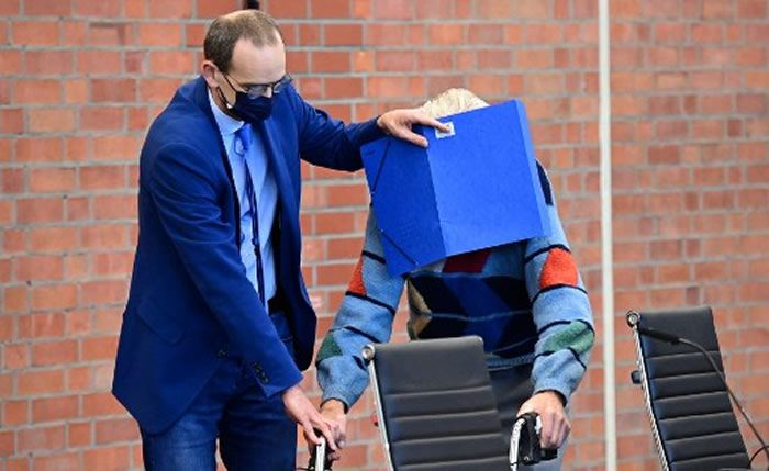 Defendant Josef S gets help from his lawyer Stefan Waterkamp (L) to hide his face behind a folder as he arrives for his trial in Brandenburg an der Havel, northeastern Germany, on October 7, 2021. (Photo by Tobias Schwarz / AFP)