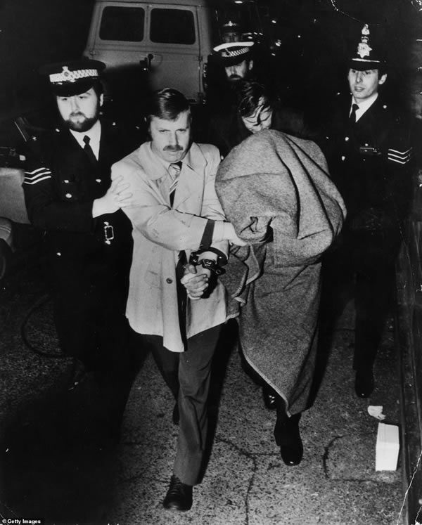 Police leading murderer Peter Sutcliffe, known as the Yorkshire Ripper, into Dewsbury Court under a blanket