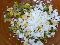3 - Mettre le four à préchauffer th 6,5 (200°). Verser le mélange poireau/échalote dans un saladier. Ecaler les oeufs durs, émietter les jaunes dans le poireau, couper les blancs en petits dés et les rajouter à la préparation avec les dés d'olives noires. Faire griller à la poêle une poignée de pignons de pin, mélanger à la préparation, rectifier l'assaisonnement si besoin.
