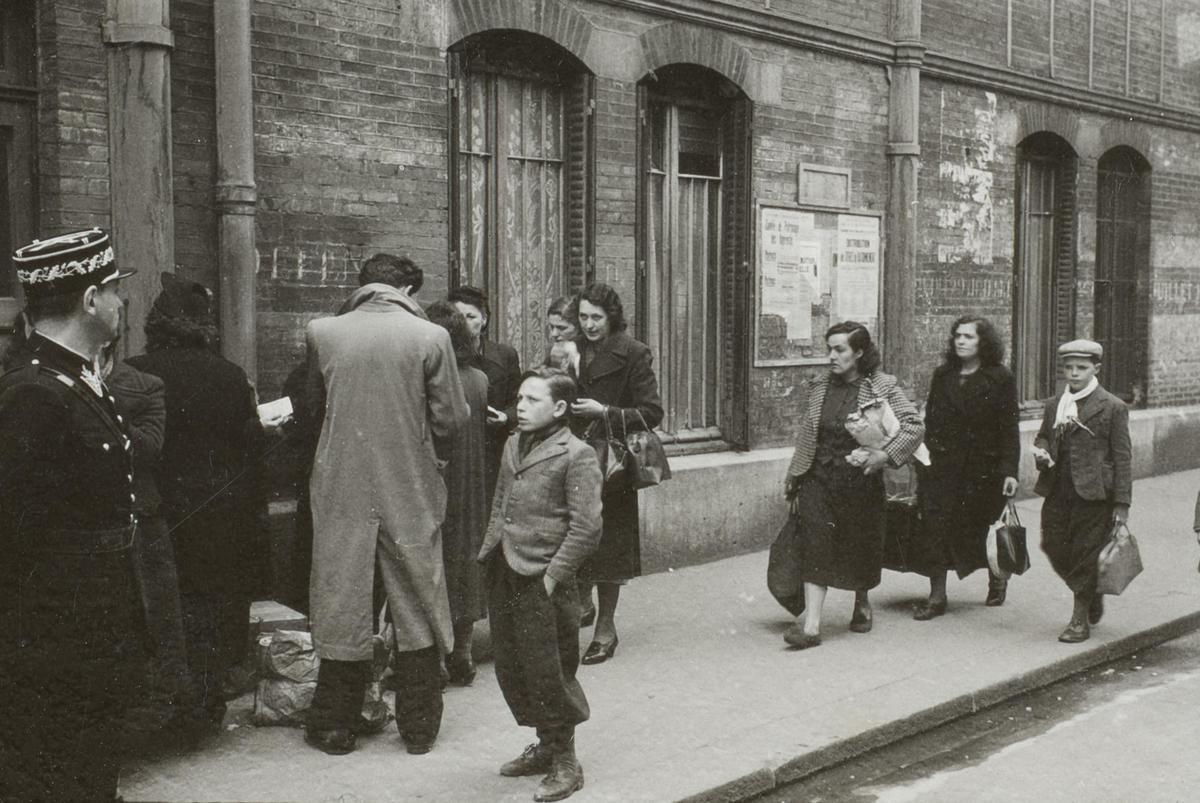 Certains hommes arrivent portant leur convocation et sont reçus par les policiers qui gardent l'entrée du gymnase Japy, à Paris, le 14 mai 1941, pendant la « rafle du billet vert ». Memorial de la Shoah