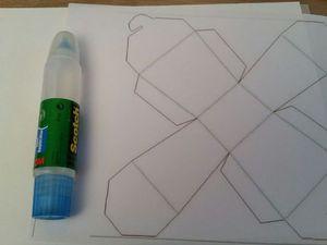 1 - Commencer en imprimant le gabarit sur une feuille fine (60 ou 80 gr) de papier A4. La coller sur la feuille cartonnée 200 gr. Vous pouvez la choisir blanche ou de toute autre couleur en fonction des teintes de votre décoration de table ou de votre sapin. Découper suivant les traits pleins (bleu foncé). Les traits en clair et pointillés matérialisent les pliages à effectuer. Découper soigneusement au cutter le petit trait rouge. Vous aider d'une règle et d'une pointe non coupante pour marquer et plier tous les pointillés. Les languettes marquées d'une croix seront à coller au dos de la croix