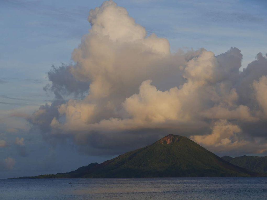 """De près comme de loin, c'est l' île- repère pour tout l'archipel et les guides touristiques évoquent souvent à son propos le mont Fuji du Japon.Toujours est-il qu'elle change de forme, de couleur selon l'île où l'on se trouve, selon la saison, selon les jours, d'heure en heure, selon qu'il pleut, que la mousson passe, que les nuages sont bas, que le coucher de soleil est clair ou sombre. En tout cas, chacun est fasciné à sa façon par ses métamorphoses perpétuelles. On la rejoint à partir du port principal de Banda Neira ( photo 16 ) sur une des petites embarcations qui font la navette. Gunung Api  signifie """" Volcan de Feu """", qui domine les îles avoisinantes du haut de ses 666 mètres. Les enfants sont contents d'accompagner les rares  touristes, le long  du chemin qui longe la côte sud de l'île. Les hommes y sont bien sûr pêcheurs mais on y cultive aussi la cannelle ( photo 20 et 21 ). Près des maisons, les tombes sont simples, proches de la mer. Ne pas se fier à son air de bel endormi: ce volcan est en activité ! Déjà en 1769 Bougainville notait dans son journal de bord qu'on trouvait aux Banda des """" fortifications respectables """" mais il ajoutait aussitôt qu' """" après quelques années, des tremblements de terre détruisent tous ces ouvrages"""" et que  """" chaque année, la malignité du climat emporte les deux tiers des soldats, matelots et ouvriers qu'on y envoie""""."""