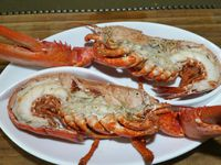 2 - Couper en 2 le homard refroidi dans le sens de la longueur. Evider la partie non comestible de la tête. Décortiquer les attaches des pinces et placer la chair obtenue dans la tête. Oter les carapaces des pinces en laissant la chair entière et intacte. Placer les 2 moitiés de homard dans un plat allant au four, redisposer les pinces à leur place initiale. Sortir le beurre d'herbes et salicorne du réfrigérateur, en déposer des rondelles sur les moitiés de homard et passer sous le grill du four pour 5 à 6 mn. Déguster bien chaud à la sortie du four soit en entrée chaude (pour 2 personnes), soit en plat principal (pour 1 personne) accompagné de riz.