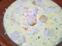 2 - Mettre le four à préchauffer th 6,5 (190°). Egoutter le riz une fois cuit, le placer dans une jatte. Râper le gingembre frais. Casser les oeufs et les incorporer dans le riz, bien mélanger. Ajouter la crème fraîche épaisse, le gingembre et les zestes de citron râpés, le sel, le poivre et le persil haché.  Ajouter à la préparation les gambas en morceaux et les noix de pétoncle dorées, mélanger le tout.