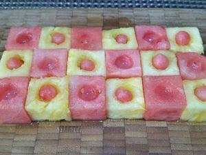 1 - Découper l'ananas et la pastèque de façon à obtenir 12 cubes de chaque très réguliers et de taille similaire. Les disposer pour former un rectangle en alternant ananas et pastèque  A l'aide d'une cuillère parisienne évider le centre de chaque cube. Placer dans les cubes d'ananas des billes de pastèque.