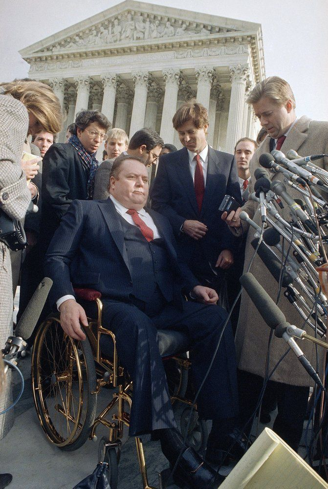 "FILE - ""Hustler"" magazine publisher Larry Flynt leave the Supreme Court building in Washington on Dec. 3, 1987, after a case was heard. Flynt, who turned ""Hustler"" magazine into an adult entertainment empire while championing First Amendment rights, has died at age 78. His nephew, Jimmy Flynt Jr., told The Associated Press that Flynt died Wednesday, Feb. 10, 2021, of heart failure at his Hollywood Hills home in Los Angeles. (AP Photo/Charles Tasnadi, File)"