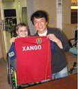 Jackie Chan sujetando una camiseta, del equipo de futbol Real Salt Lake patrocinado por XANGO, acompañado de su fan que cumplió su sueño de pasar todo un día con él, CUMPLE TAMBIÉN TUS SUEÑOS!