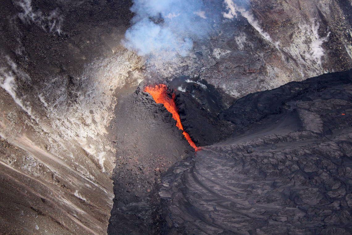 Kilauea - Halema'uma'u - A cone of cool dark lava splash has built up around the fountain's vent and its turbulent outlet channel to the lava lake. - USGS photo taken by M. Zoeller on 01.12.2021 - One click to enlarge