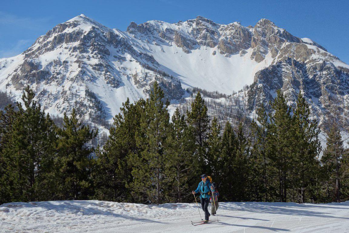dans la montée au col de l'Izoard versant sud, skis sur le sac, parmi bébé tracté en luge, VTTistes, piétons, skieurs de fond, lugistes...