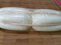 """1 - Mettre les oeufs à cuire dans une casserole d'eau pendant 9 mn pour qu'ils deviennent durs. Les sortir de l'eau et les écaler de suite. Les placer par 2 sur du film étirable """"dos à dos"""", côté pointu le l'oeuf vers l'extérieur, et commencer à les enrouler dedans, Disposer les 5 piques en bois sur le film étirable en les espaçant de 1 cm environ (comme sur la photo) et continuer à enrouler les oeufs avec les piques sur quelques tours encore. Placer un élastique à chaque extrémité des oeufs pour maintenir l'ensemble, puis serrer le tout avec des liens en silicone de façon à ce que les piques en bois fassent pression sur les oeufs et s'enfoncent un peu dans le blanc. Mettre au réfrigérateur pendant 1 h pour que les oeufs prennent la forme."""