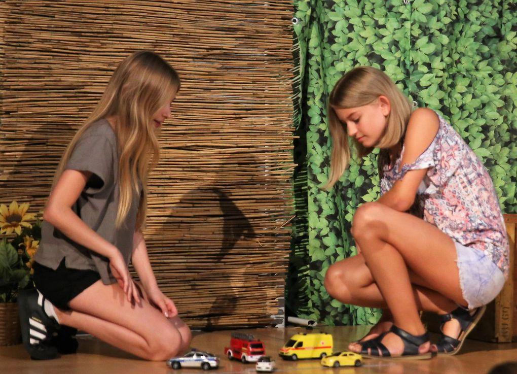 """Auch die Nachbarskinder Jane (Letitia Eder) -  rechts -  und Mary (Sarah Benz) lassen bei ihrem Lieblingsspiel """"schwerer Verkehrsunfall"""", das sogar die Dorfpolizisten mit gezogener Pistole auf den Plan ruft, Lizzie außen vor."""