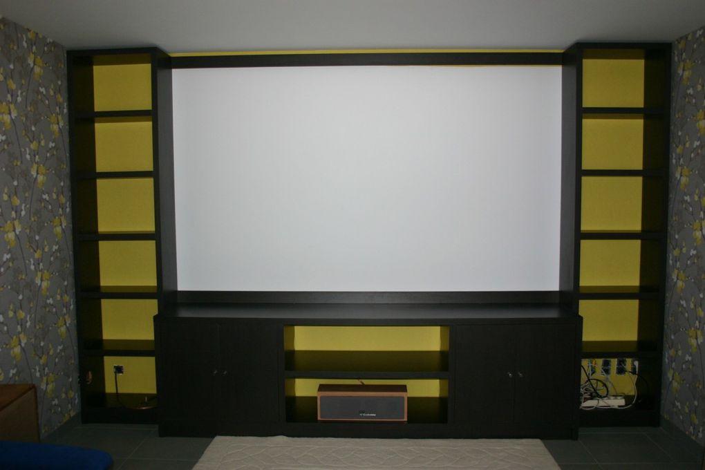 Un agencement moderne en Medium alvéolaire et stratifié chêne foncé, pour une salle de ciné privée.