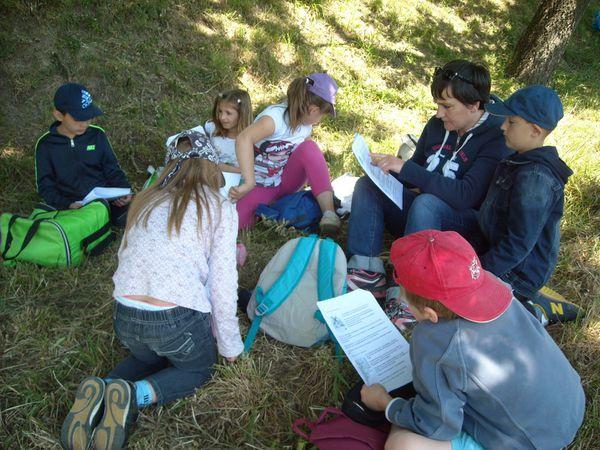 En fin de journée ,c'est l'heure du bilan : se  mettre  à l'abri du vent pour lire et compléter un dossier de jeux et questions sur le moulin !
