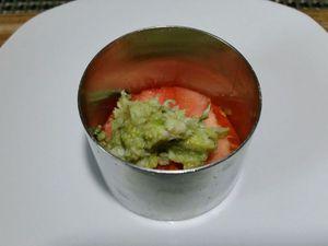 2 - Monter votre entrée sur un plat de service en  alternant dans l'emporte-pièce rond une rondelle de tomate, une couche d'avocat/crabe, une couche de rondelles de surimi, une deuxième rondelle de tomate, une autre couche d'avocat/crabe et une dernière rangée de rondelles de surimi bien égalisée. Retirer délicatement l'emporte-pièce.