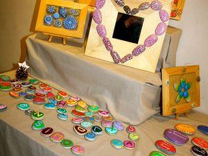 """Ariane Vigne a créé sa marque """"Framboise Indigo"""" et s'est surtout fait connaitre avec ses petits galets de la Drôme qu'elle peint et décline en tableaux, en magnets mais aussi en jeux de mémo pour enfants (testés et approuvés par la maison!!!). Avec cette Montilienne débordante d'imagination, tout est propice à la création. Ainsi, elle réalise aussi des bijoux en billes de verre, des barrettes en feutrine, le tout décliné dans des couleurs toujours très joyeuses. Les noisettes, les pommes de pins, la nature en général... tout est chez elle propice à la créativité. Vous l'aurez compris... je suis fan! (Photos G.V.)"""