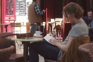 Homme lisant à la terrasse d'un café