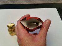3 - Tracer sur une feuille de papier des traits parallèles pour former une bande de 5mm environ, la remplir au marqueur noir et la découper soigneusement. Voilà une ceinture pour l'habit du père noël qu'il ne vous reste plus qu'à fixer à la colle sur son corps. Terminer par un petit point noir au marqueur sous le menton du personnage pour matérialiser le bouton du manteau. Réouvrir sa base pour y glisser un chocolat, une friandise ou un petit gadget et refermer. Votre père noël est terminé et il cache une petite surprise !!